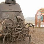 a-mud-caked-van-crosses-the-arctic-circle-on-the-dempster-highway