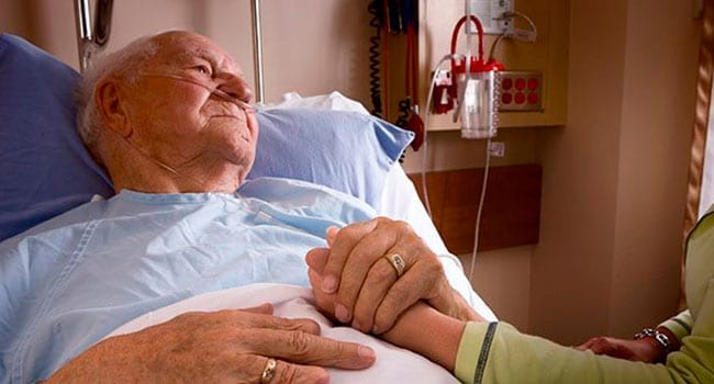 Old man lying in hospital bed holding daugher