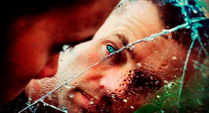 Man looking through cracked glass