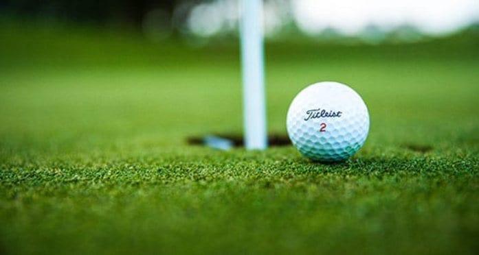 Golf ball teetering on hole