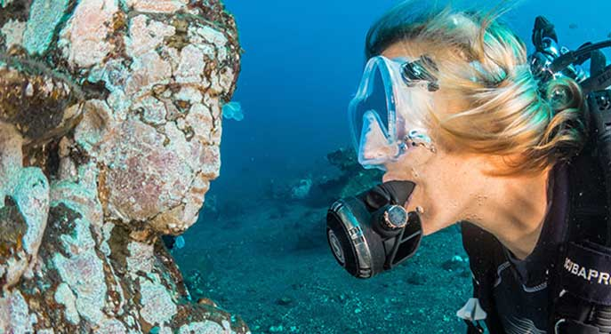 Diver face to face with sculpture